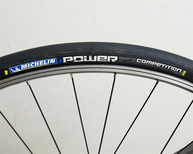 Michelin Power Competition road bike tire on a rolling resistance test machine