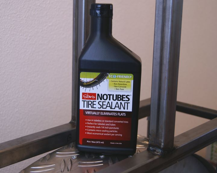 Bottle of Stan's NoTubes tubeless sealant on a rolling resistance test machine